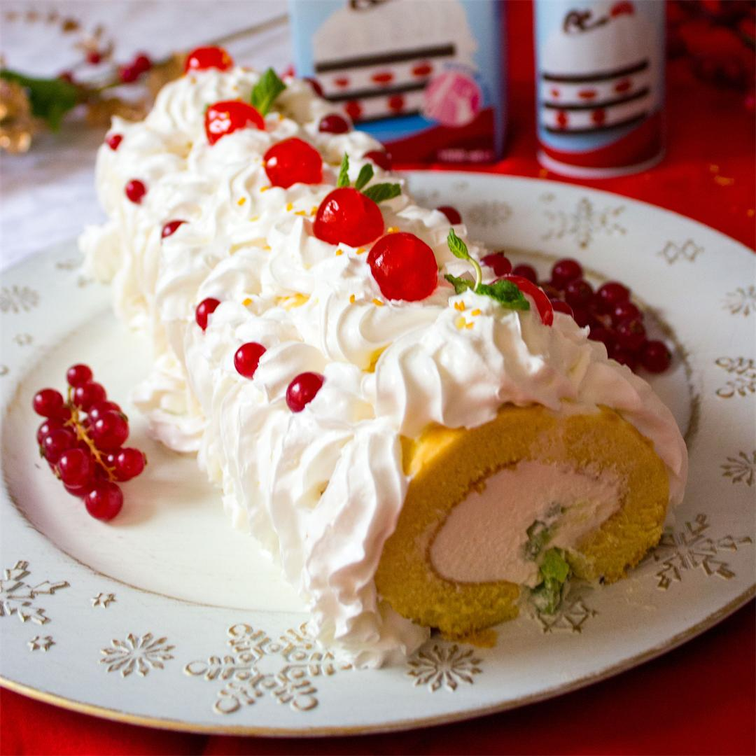 Whipped cream charlotte cake roll with fresh and candied fruits