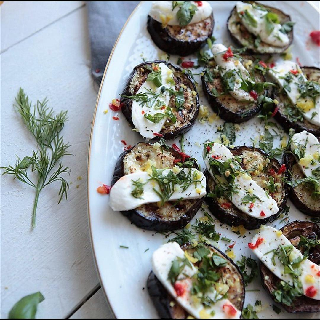 Mini eggplants pizzas with mozzarella and green herbs