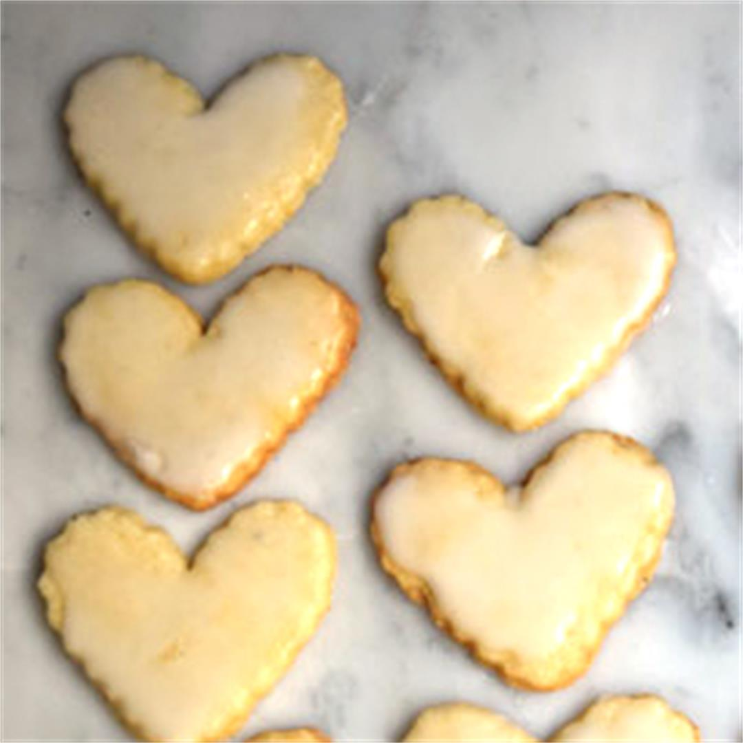 Lemon shortbread hearts are glazed with lemon frosting.