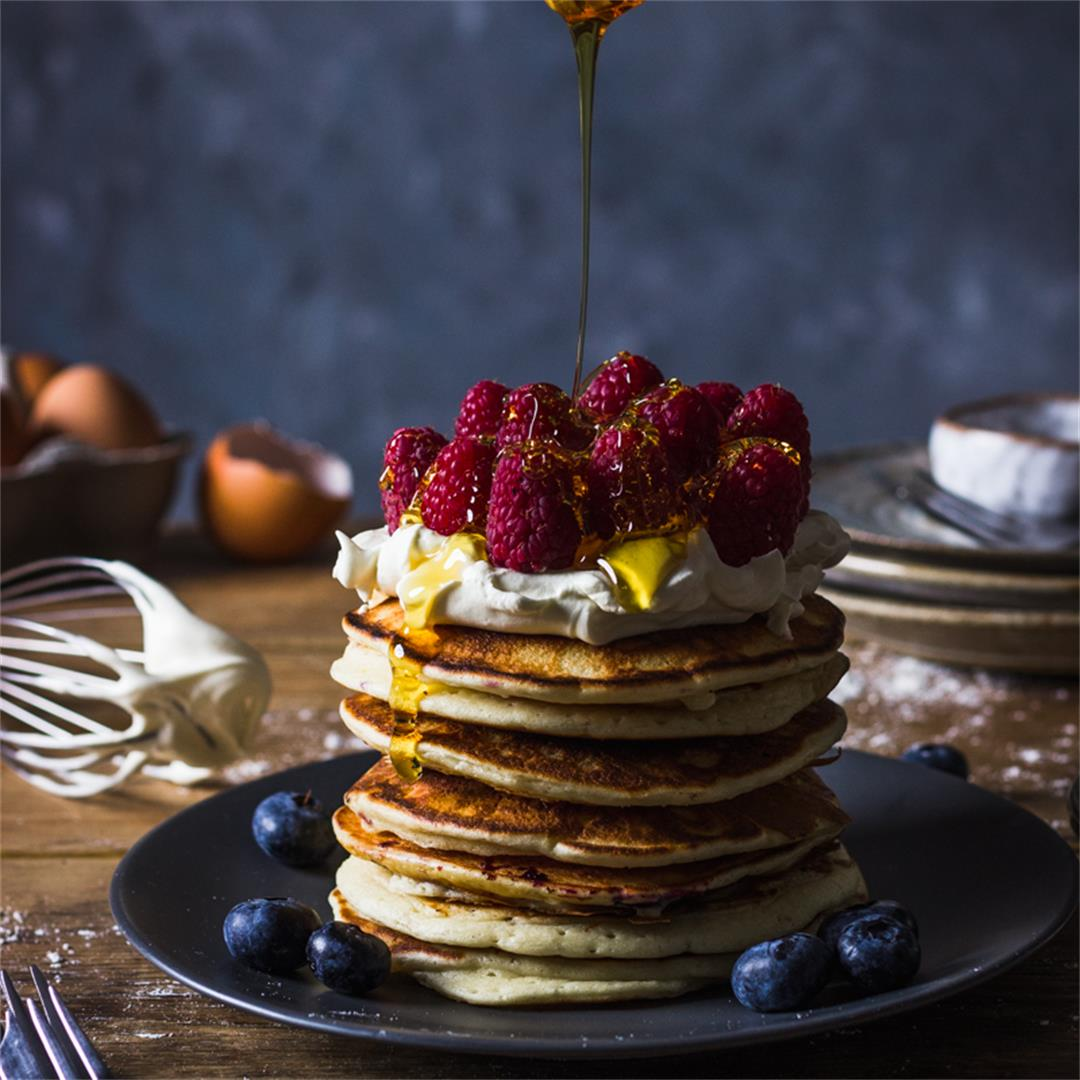 American blueberry pancakes stacked with raspberries and cream
